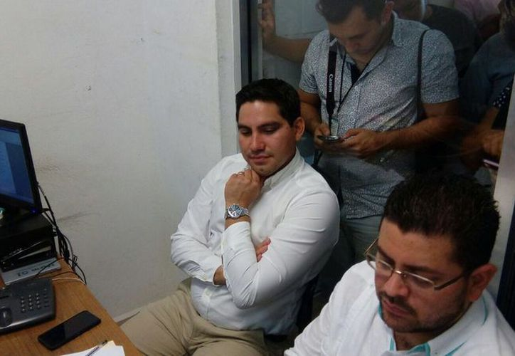 """Jesús Pérez Ballote (al centro, sentado) comparece ante la FGE por una denuncia en su contra. Una persona de nombre Roger Moo, a quien el dirigente panista había citado como su """"testigo"""" en el caso de las calles de Mérida dañadas con ácido, lo demandó."""