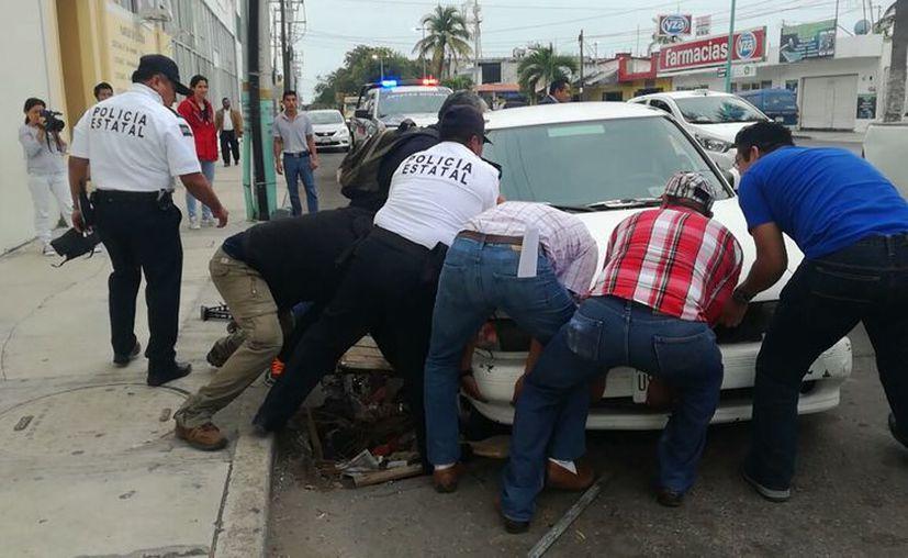 Vecinos y policías trabajaron juntos para sacar el carro de los hoyos, que dejaron al descubierto una profunda caverna. (Foto: Redacción/SIPSE)