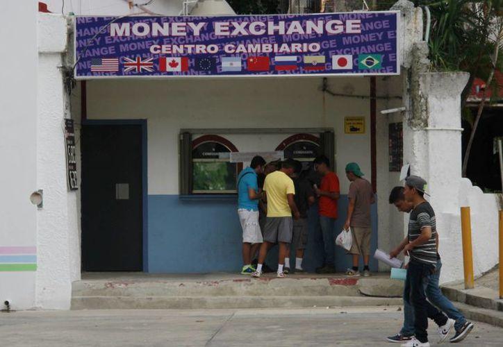 El tipo de cambio del peso frente al dólar continúa volátil. (Luis Soto/SIPSE)