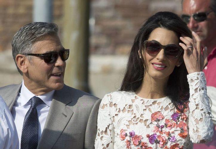 George Clooney y Amal Alamuddin al salir del hotel Aman en Venecia, donde se casaron anoche. (Agencias)
