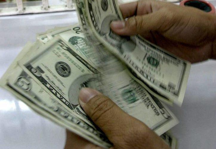 De acuerdo con datos de la Condusef, en 2013 se recibieron 21 mil 597 millones de dólares por concepto de remesas enviadas a México. (Archivo/EFE)