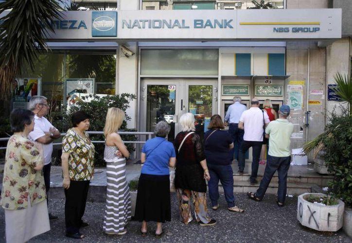 Un grupo de personas hacen cola para utilizar un cajero automático en el exterior de una oficina bancaria cerrada, en Atenas, el 30 de junio de 2015. (Foto AP/Thanassis Stavrakis)