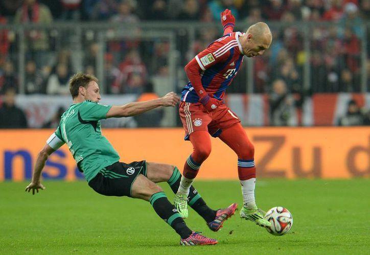 El Bayern Munich, que tuvo una primera vuelta invicto en la Bundesliga, ahora empató y suma dos partidos sin ganar. En esta foto Arjen Robben (d) y Benedikt Hoewedes, de Schalke, pelean por el balón. (Foto:AP)