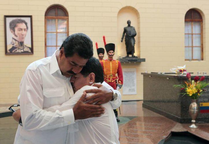 Imagen difundida por el Palacio de Miraflores, que muestra a Nicolás Maduro y a Diego Armando Maradona abrazados ante la tumba del expresidente Hugo Chávez, el sábado. (Agencias)