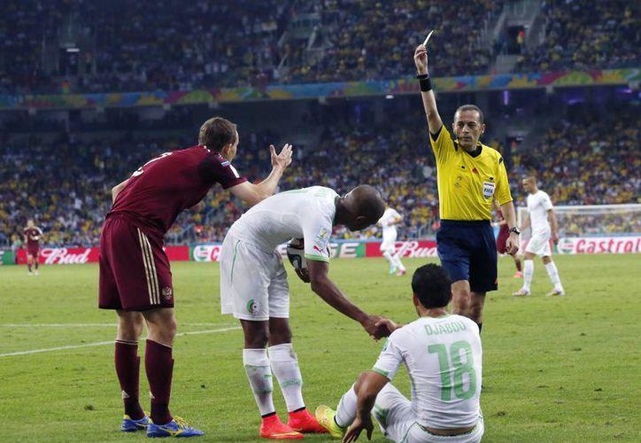 El arbitro Cuneyt Cakir muestra el cartón preventivo al ruso Alexei Kozlov en el partido contra Argelia. (Foto: AP)