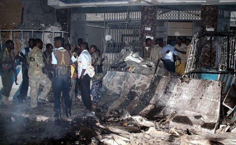 Varias personas se acercan al lugar donde estalló un artefacto en uno de los dos ataques de la milicia yihadista somalí Al Shabab contra un hotel en Mogadiscio, Somalia. (EFE)  Un atacante suicida embistió con su coche cargado de explosivos el perímetro de protección de un hotel muy conocido en la capital somalí el domingo
