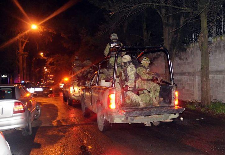 Militares al momento de llevarse a decenas de elementos de autodefensa de Aquila, Michoacán. (Notimex)