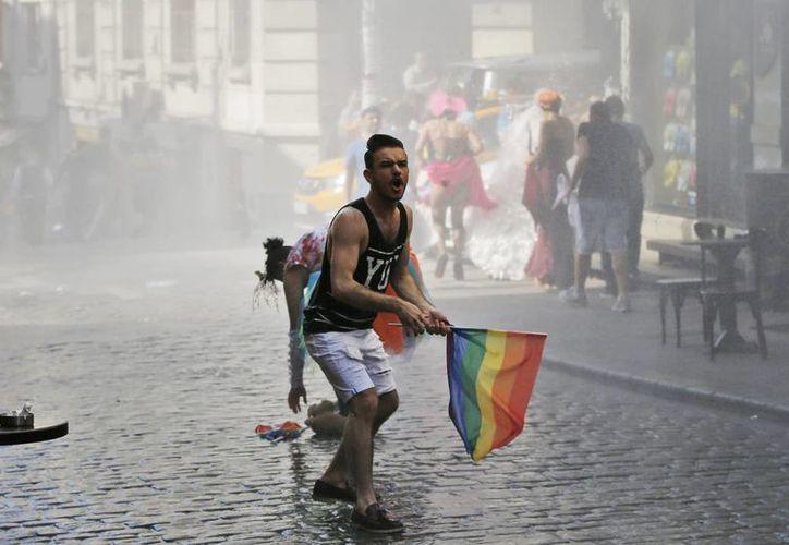 Un participante en el evento del Orgullo Gay para apoyar los derechos de Lesbianas, Gays , Bisexuales y Transexuales (LGBT ) huye después que la policía turca utilizó un cañón de agua para dispersarlos en Estambul, Turquía. (AP)