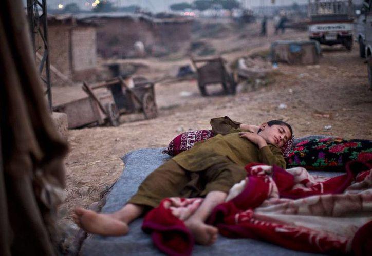 El conflicto en Pakistán -que este viernes dejó al menos 15 extremistas muertos por ataques aéreos del Ejército- causa 'otras' víctimas: los desplazados, como el joven de la imagen, quien descansa en un sitio, lejano a su hogar. (AP)