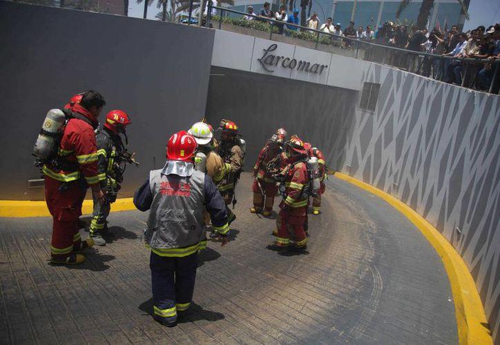 Bomberos peruanos auxilian a personas heridas en el centro comercial Larcomar, uno de los centros comerciales más exclusivos de Lima, que se incendió este miércoles. (EFE)