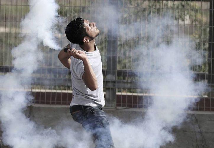 Un palestino lanza gas lacrimógeno contra soldados israelíes durante un enfrentamiento cerca del cruce de Erez, en el norte de la Franja de Gaza, Palestina. (EFE)