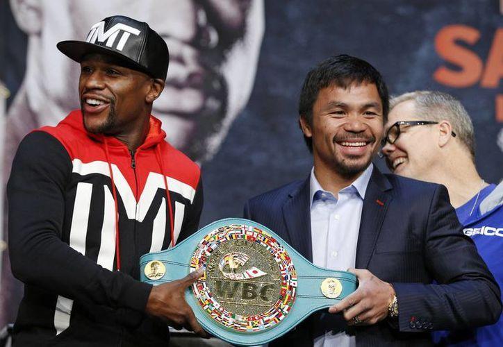 El invicto Floyd Mayweather Jr y Manny Pacquiao sostienen el cinturón de esmeraldas que ganará uno de los dos este sábado. (Fotos: AP)