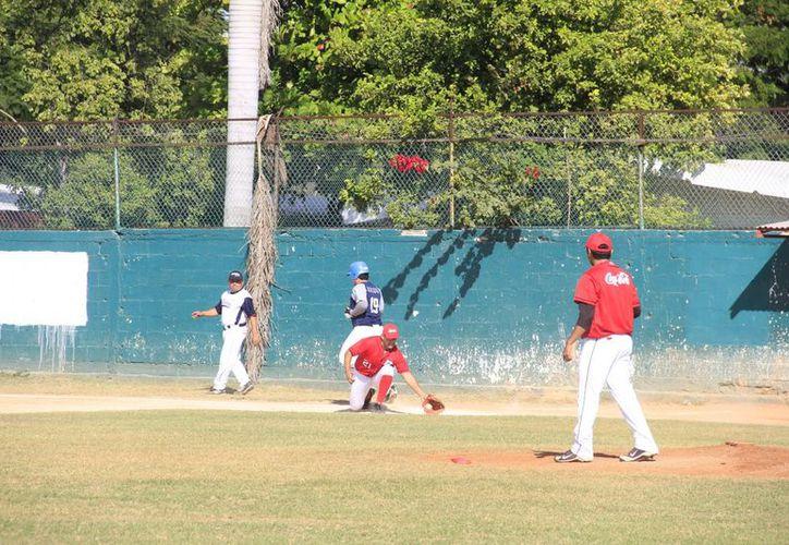 Héctor Castañeda pone fuera de combate a un rival en primera base. (Marco Moreno / SIPSE)