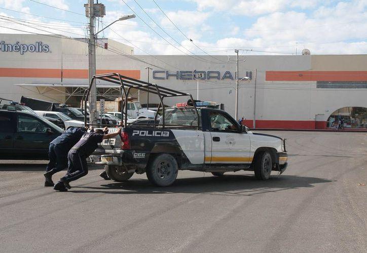 Los policías municipales empujan la patrulla 7118 para encender el motor. (Julián Miranda/SIPSE)