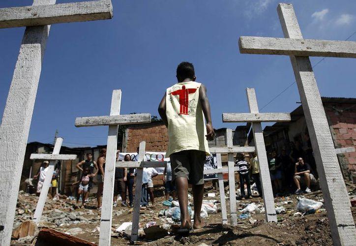 Un niño camina entre unas cruces durante una protesta contra un asesinato en Río de Janeiro, Brasil. (EFE/Archivo)