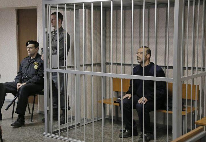 Activista de Greenpeace, Dmitry Litvinov, dentro de una jaula en una sala del tribunal en Murmansk, Rusia. (Agencias)