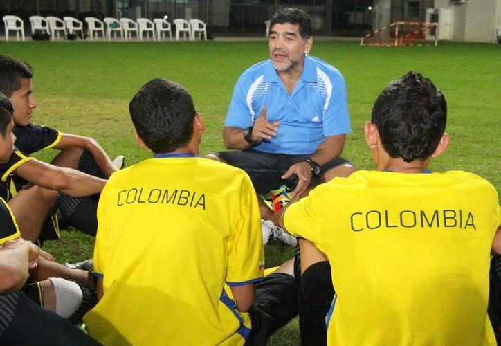 Diego Maradona durante un encuentro con jóvenes futbolistas coloimbianos en Emiratos Árabes Unidos. (Foto de archivo de Notimex)