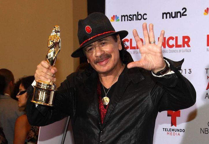Santana con su Premio al Compromiso Sobresaliente por la Causa y la Comunidad. (Agencias)