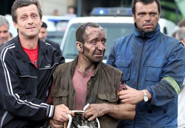 Un minero bosnio es atendido por familiares y miembros de los servicios de rescate, tras salir del pozo minero de Raspotocje, en Zenica, Bosnia. (EFE)
