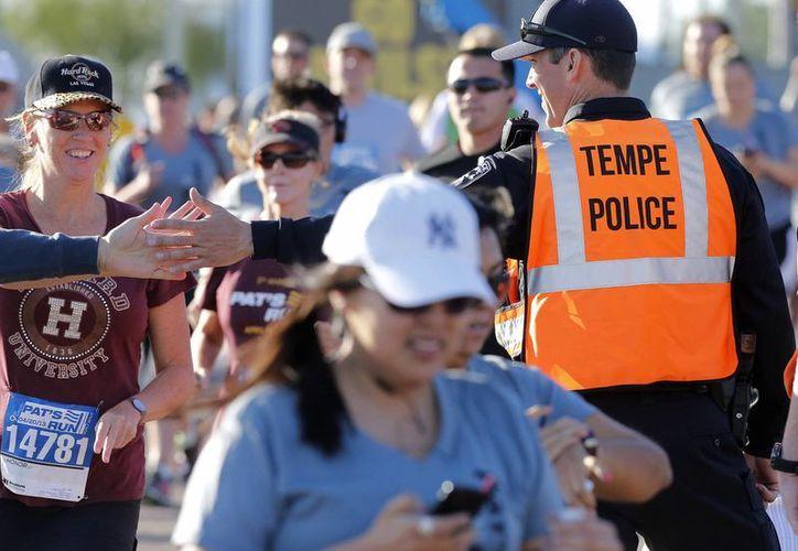 Un atleta saluda a un policía durante la carrera anual de  Tempe en Arizona, EU. (Agencias)