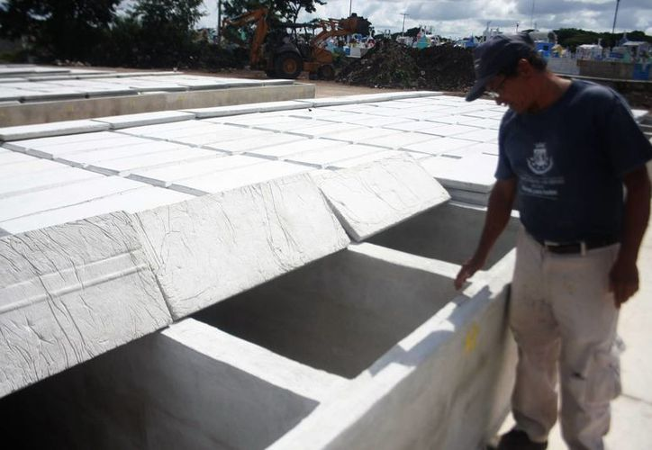 En el cementerio Xoclán se concentra el 90 por ciento de las inhumaciones que se realizan en la ciudad de Mérida. En la imagen, un trabajador muestra las fosas del lugar.(Milenio Novedades)