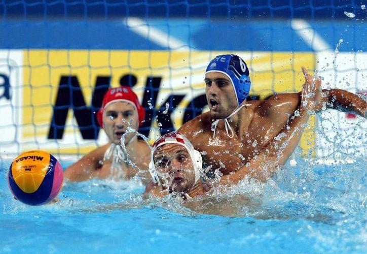 El croata Luka Loncar (c) disputa el balón con el griego Kyriakos Pontikeas (d) hoy, jueves 6 de agosto de 2015, durante un partido por la semifinal de polo acuático de los Campeonatos Mundiales de Natación, en Kazán (Rusia). Croacia venció 15-13. (EFE)
