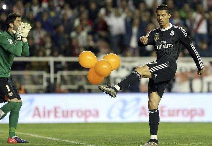 El delantero portugués del Real Madrid, Cristiano Ronaldo (d), golpea unos globos lanzados por aficionados en el encuentro frente al Rayo Vallecano correspondiente a la jornada 30 de la Liga de España. Real Madrid intenta que Cristiano no se pierda el juego ante Eibar debido a acumulación de amonestaciones. (EFE)