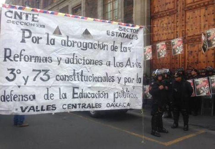 Integrantes de la CNTE y policías, frente a las instalaciones de la SEP. (Milenio)