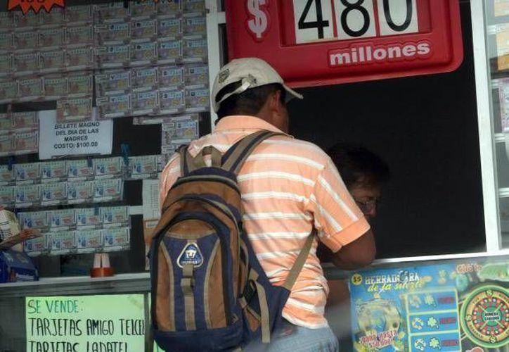 Con frecuencia, la Lotería Nacional reparte premios en Yucatán. En la imagen, un cliente compra un billete en un expendio. (Milenio Novedades)