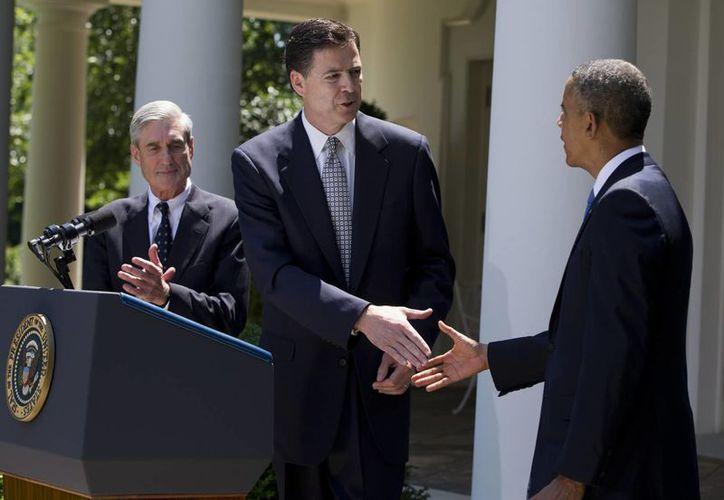Obama estrecha la mano de James Comey después de anunciar su nominación para tomar el lugar de Robert Mueller (izq). (Agencias)