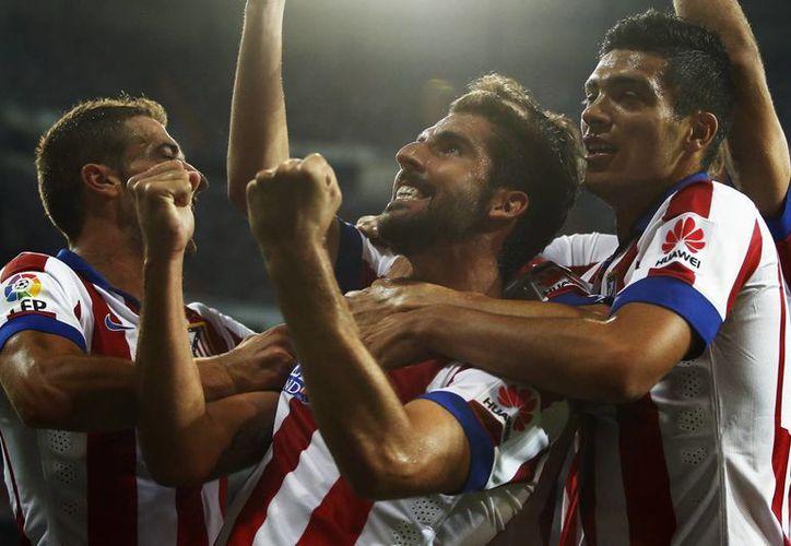 El mexicano Raúl Jiménez felicita junto con sus compañeros a Raúl García quien anotó el tanto del empate al 87. (Foto: AP)