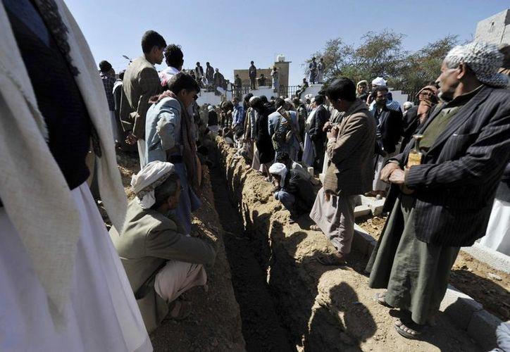 Yemeníes esperan para enterrar los cuerpos de los miembros del movimiento chií yemení de los hutíes que fueron asesinados. (EFE/Archivo)