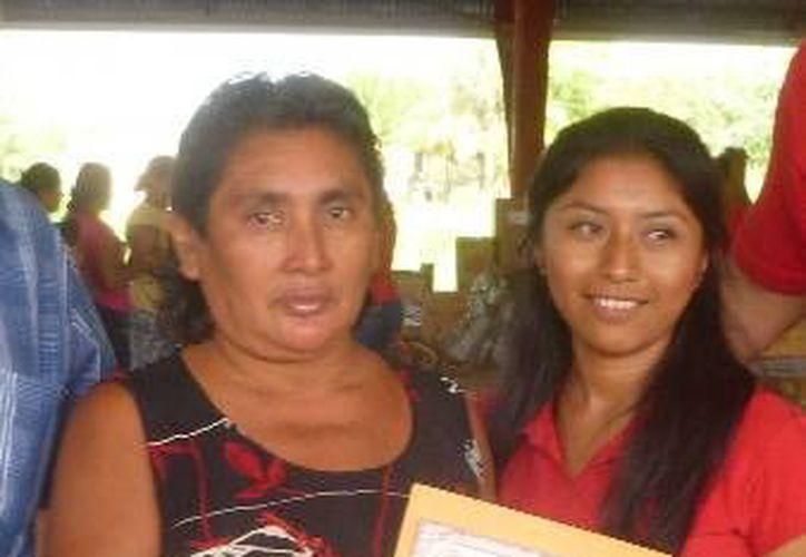 La beneficiada recibió el documento de la representante del programa de gobierno. (Raúl Balam/SIPSE)