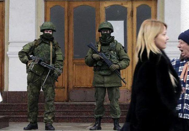 Hombres vestidos de militares en la puerta de un edificio en Ucrania.  (EFE/Archivo)