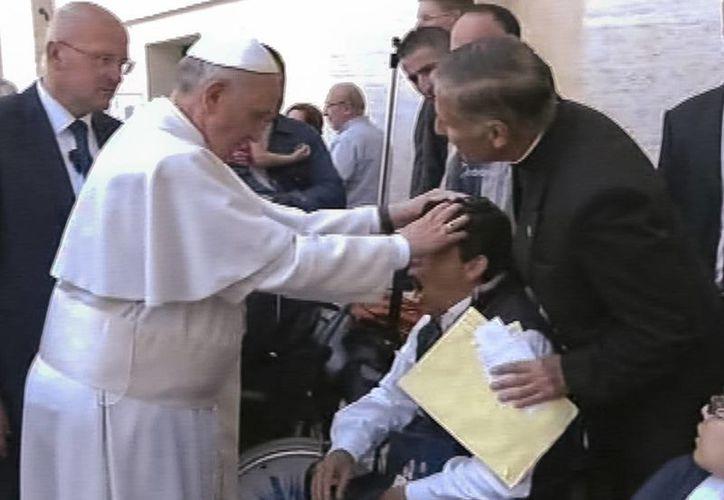 Momento en que el Papa ora ante el muchacho, en la Plaza San Pedro, cerca del Arco de las Campanas, el pasado domingo. (Foto: APTN/AP)