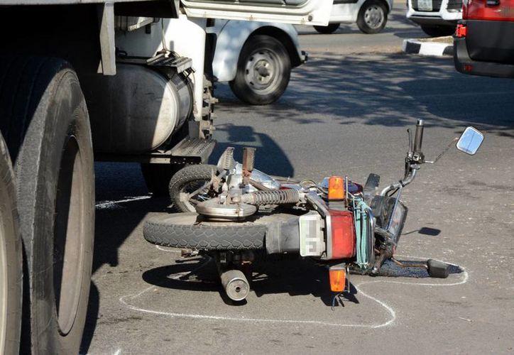 La pesada unidad casi le pasa encima al conductor de esta motocicleta, en el fraccionamiento Francisco de Montejo. (Milenio Novedades)