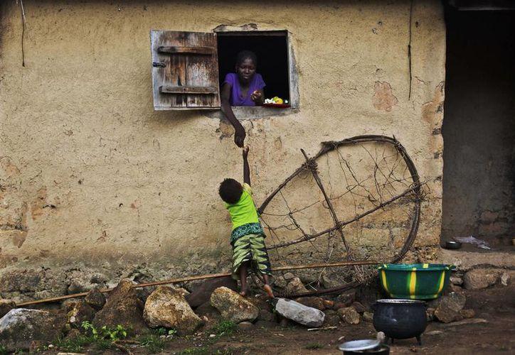 Una mujer le pasa comida por la ventana a un niño en Meliandou, pueblo de Guinea que se cree es la cuna del nuevo brote de ébola. (Agencias)