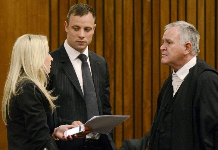 Oscar Pistorius (de frente) presta atención a dos miembros de su equipo de abogados en la Corte de Pretoria, donde será condenado dentro de pocos días por homicidio. (Foto: AP)
