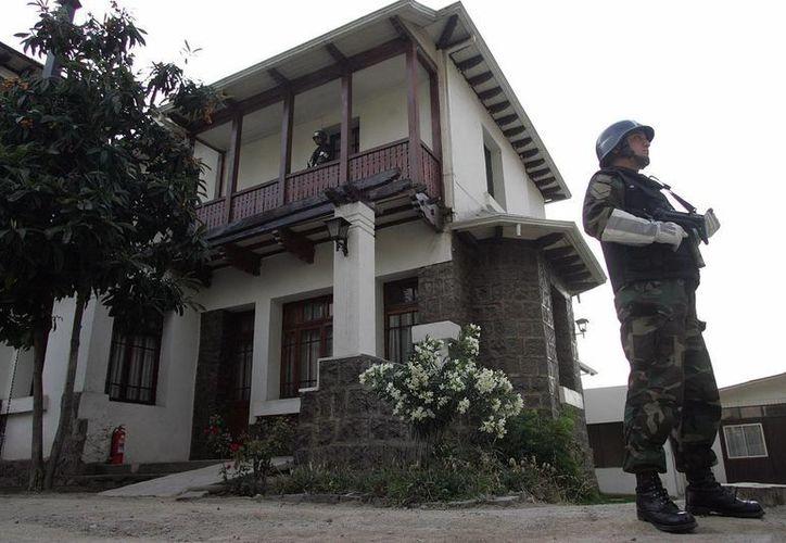 Un policía militar hace guardia frente a una de las casas del interior del penal Cordillera, a las afueras de Santiago, Chile. (Archivo/EFE)
