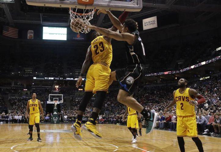 Malcolm Brogdon logra una canasta pese al esfuerzo de LeBron James. Al final los campeones Cavs se impusieron a Bucks. (AP)
