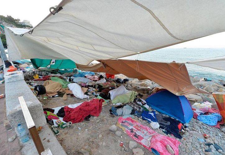 Una barcaza en la que viajaban un número aún no determinado de ilegales se volcó frente a las costas de Libia. La imagen no corresponde al hecho; se trata de inmigrantes ilegales que descansan en las playas de Ventimiglia, Italia, luego de ser rescatados. (Efe/Archivo)