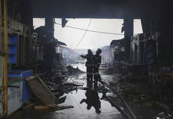 Dos bomberos inspeccionan los daños de un edificio tras un incendio.  Al menos cinco personas murieron al derrumbarse un edificio de viviendas, debido a una explosión de gas. (EFE/Archivo)