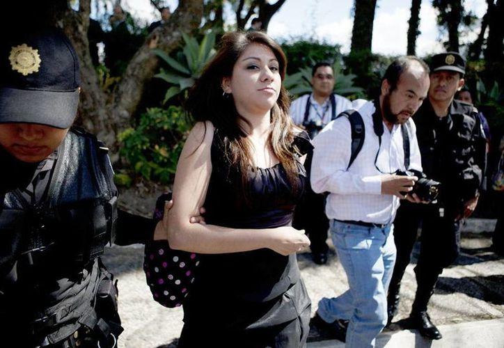 Una mujer no identificada (centro) es capturada en la Ciudad de Guatemala, Guatemala, por lanzar un polvo blanco a la vicepresidenta de ese país, Roxana Baldetti, cuando se retiraba del Teatro Nacional Miguel Ángel Asturias. (EFE)