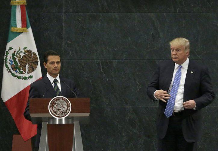 El presidente Enrique Peña Nieto y el candidato republicano a la presidencia de EU, Donald Trump, al finalizar la rueda de prensa que ofrecieron en Los Pinos. (AP/Marco Ugarte)
