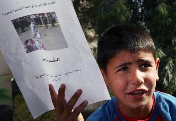 Un niño sirio muestra la imagen de una decapitación mientras participa en una manifestación en Damasco, Siria, para protestar por la decapitación de los sirios en Arabia Saudí después de ser acusados de narcotráfico. (Agencias)