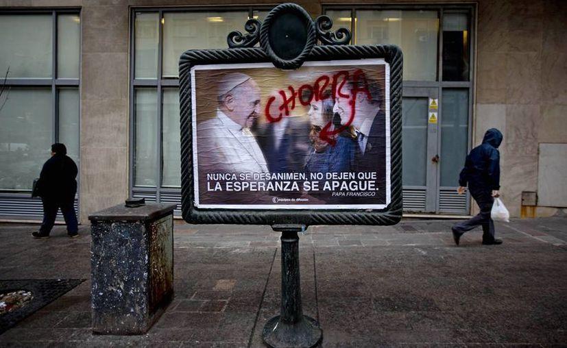 Peatones caminan detrás de un afiche vandalizado donde se ve al papa Francisco, a la presidenta argentina Cristina Fernández y al político oficialista Martín Insaurralde. (Agencias)