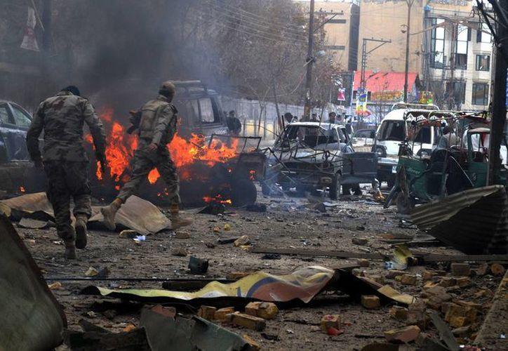 Soldados de la fuerza paramilitar paquistaní revisan la zona donde estallo una bomba junto a un autobús. (Agencias)