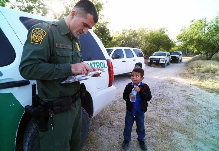 Imagen del oficial Ortiz y el pequeño Alejandro en la zona fronteriza del Valle del Río Grande, en la orilla norte del Río Bravo, al sur de Texas. (nytimes.com)