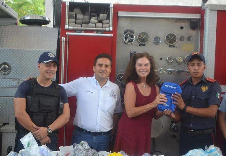 Nancy Ellen Walker, en representación de un grupo de compatriotas suyos, entregó a los bomberos equipo valuado en más de 300 mil pesos.  (Redacción/SIPSE)