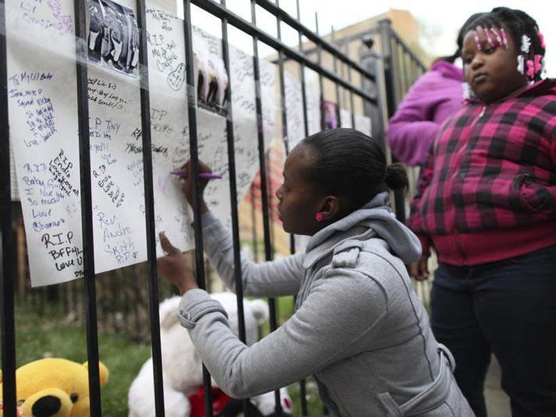 Family and friends of Endia Martin sign posters at a memorial for the slain 14-year-old in Chicago.